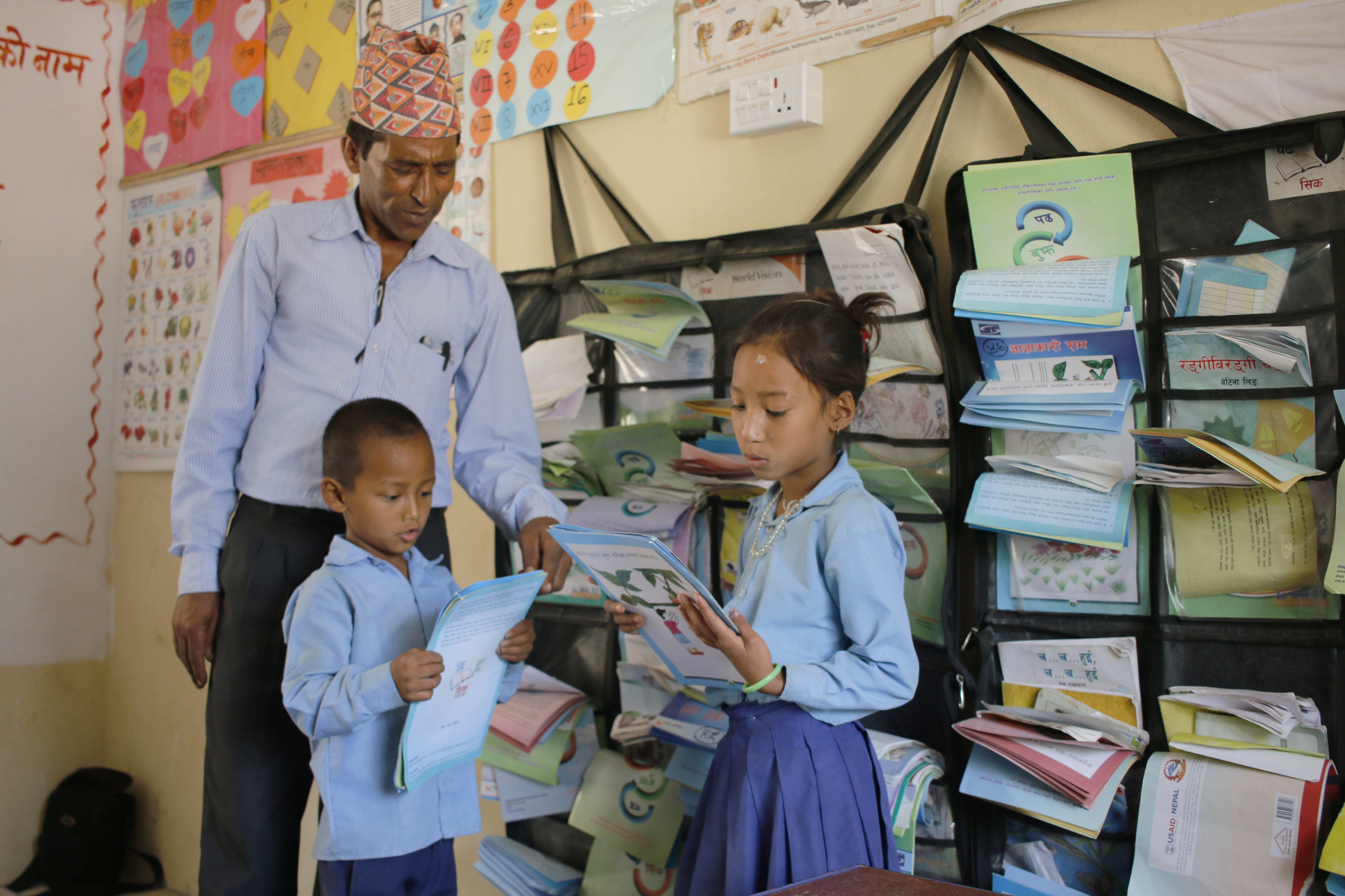 Nine year old Phadindra (boy) and eight year old Purna Kumari read books from the reading corner while Nil Prasad guides them.
