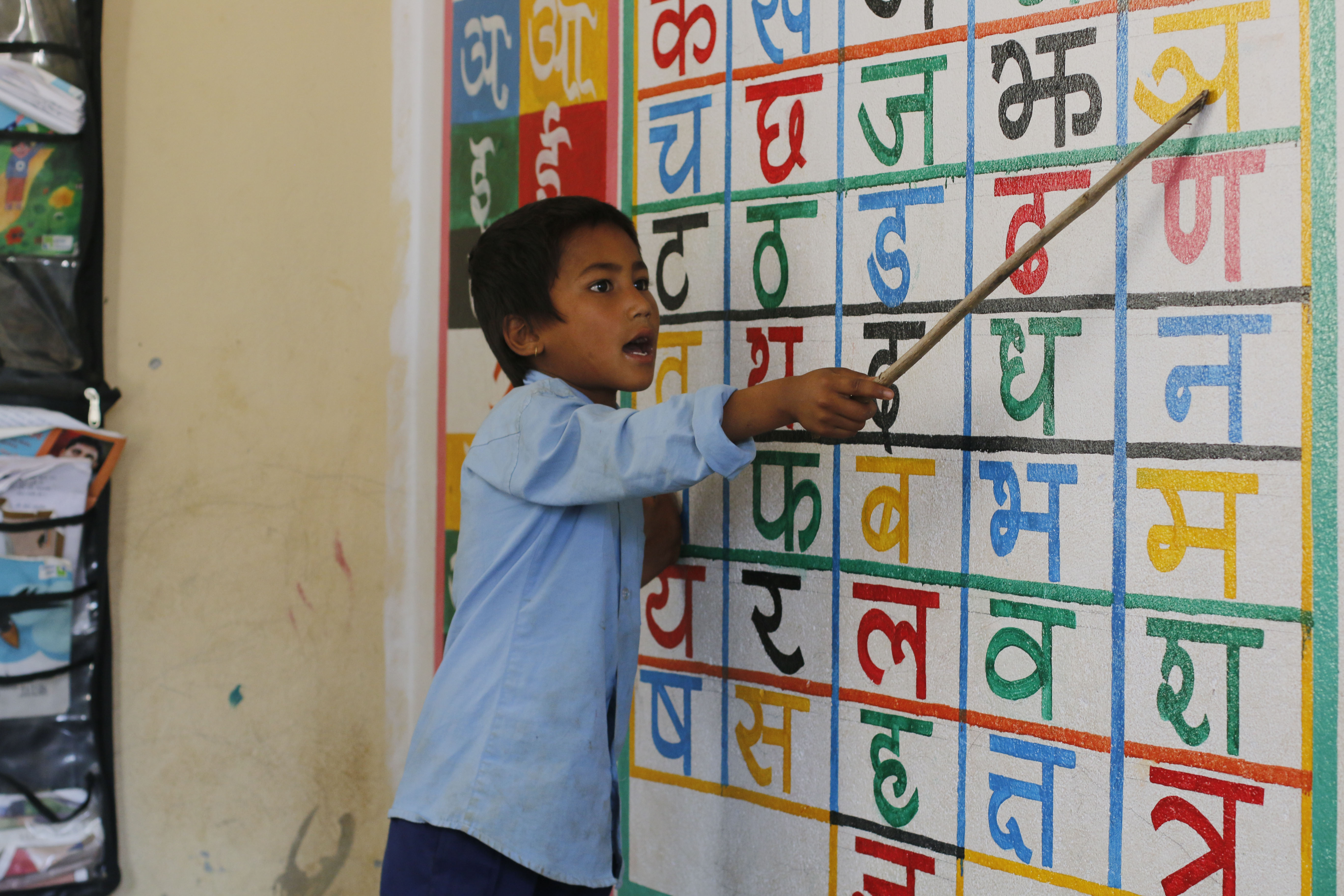 Hom Bahadur, a first grader, enthusiastically leads his friends in a class activity.
