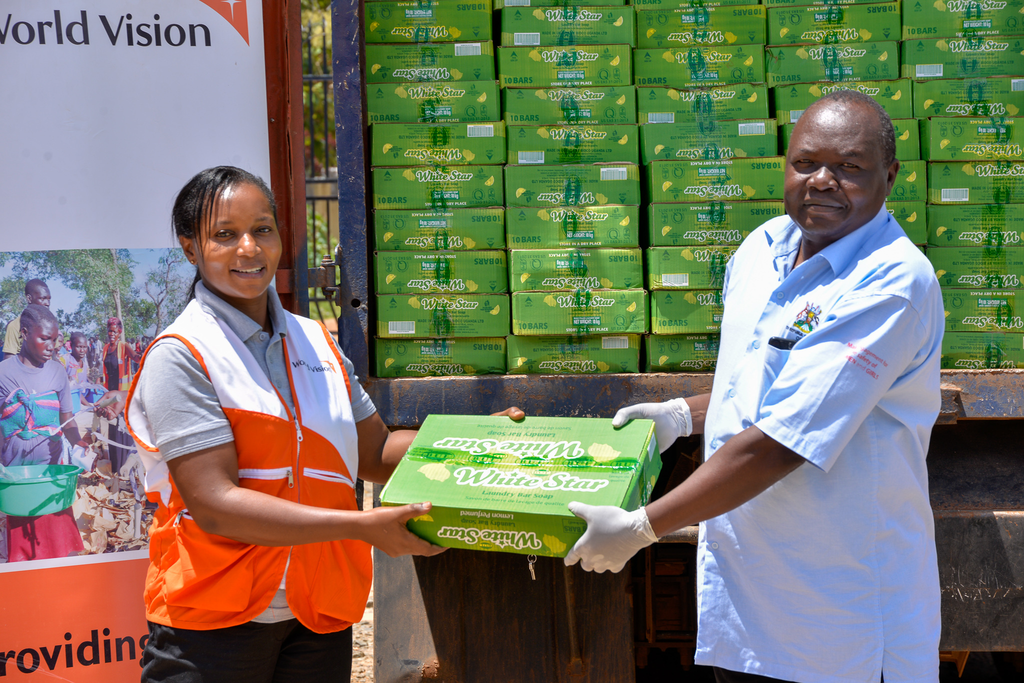 The Refugee Response Director, Mary Njeri handing over soap to an official from the Office of the Prime Minister