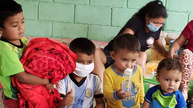 Francisca's grandchildren look through the emergency kits at their shelter