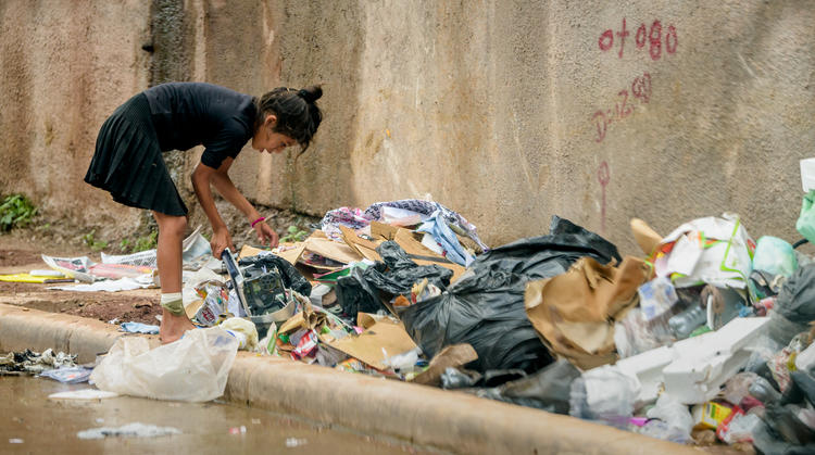 Girl sifting through plastic waste