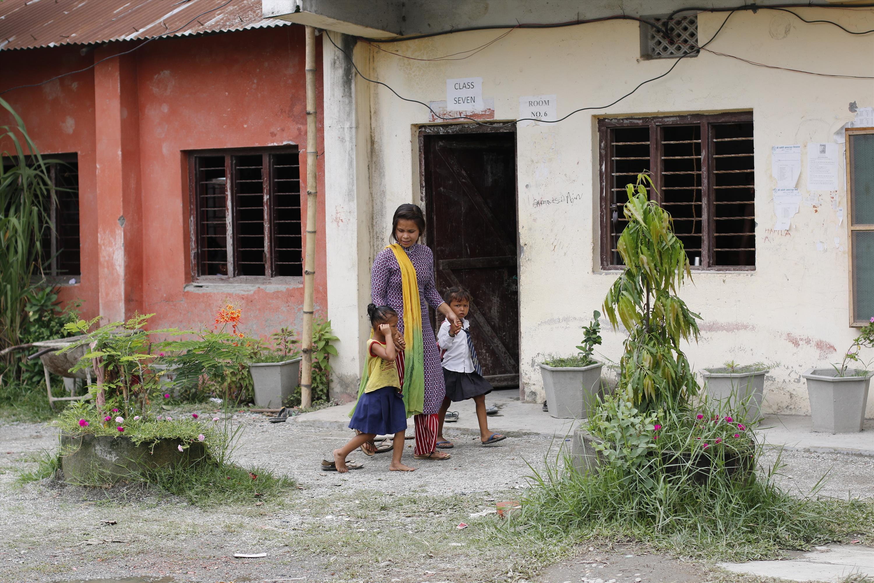 Prabha guides the two children to their classes
