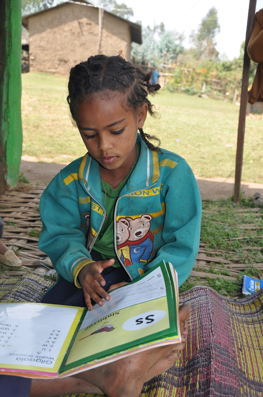 Giduma's 8-year-old sister is learning to read as well