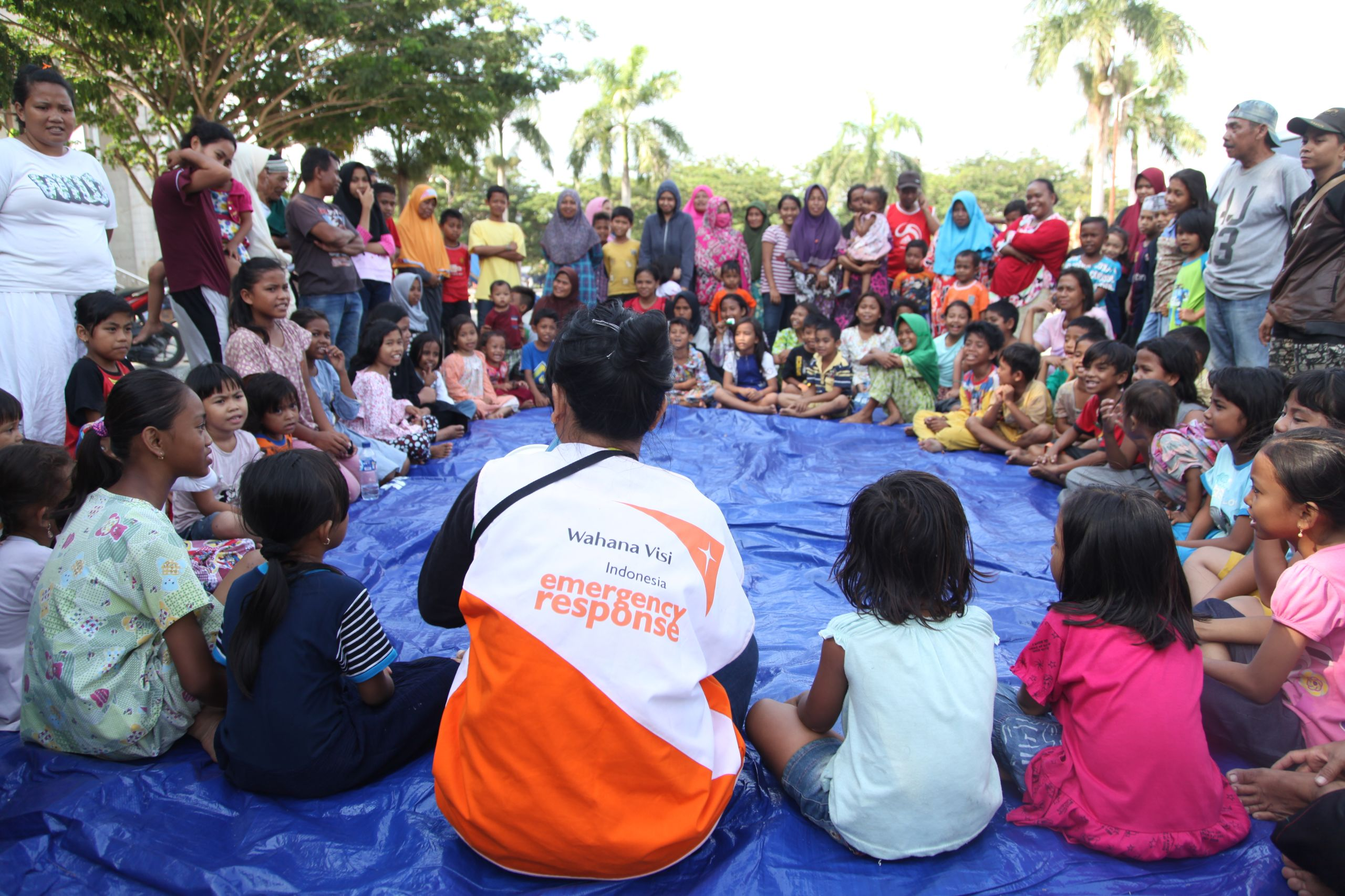 "<alt=""World Vision Indonesia emergency response member gathered with children and their families in a circle"">"