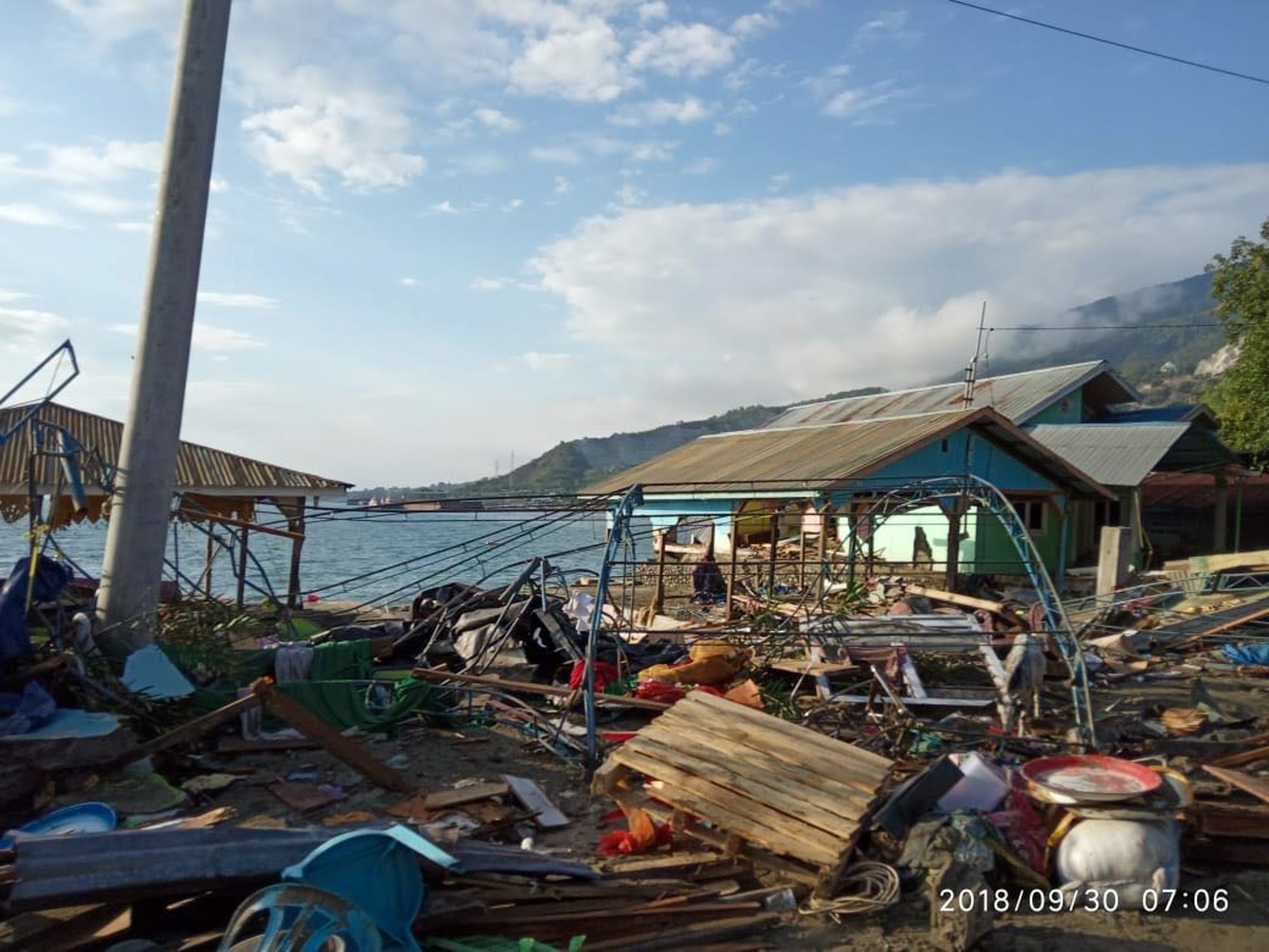 "<alt=""View of collapsed building along the coast in Palu, Indonesia"""