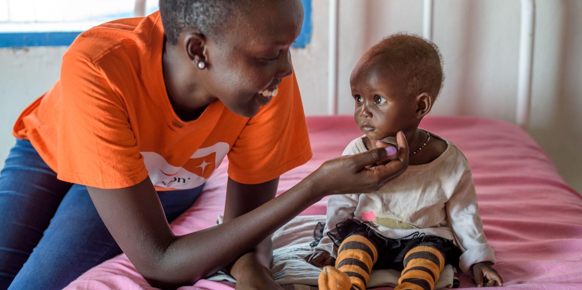 "<alt=""World Vision staff helping malnourished child"">"