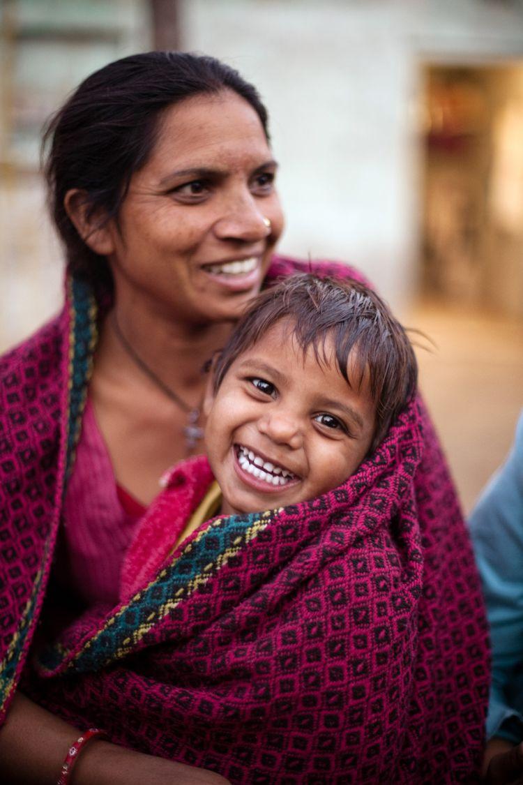 "<alt=""A mother holding her smiling child"">"