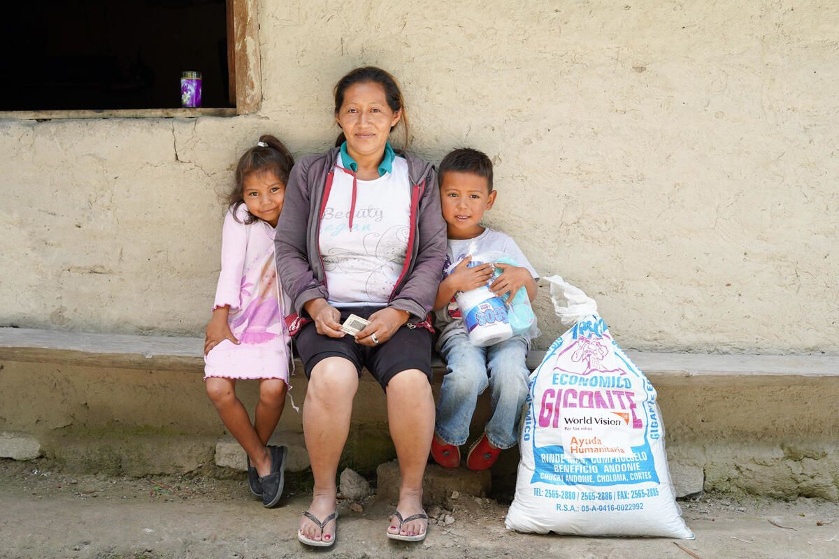family in Hondras sits with food support provided by World Vision