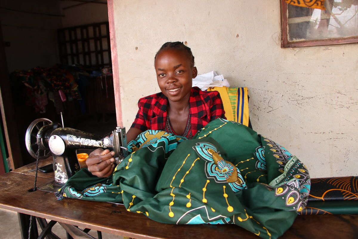 Mwila, sponsored child, sits at the sewing machine in Zambia