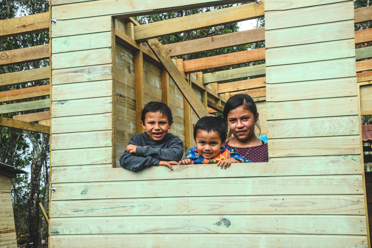 Elquin and his siblings in the window of their new home in Honduras