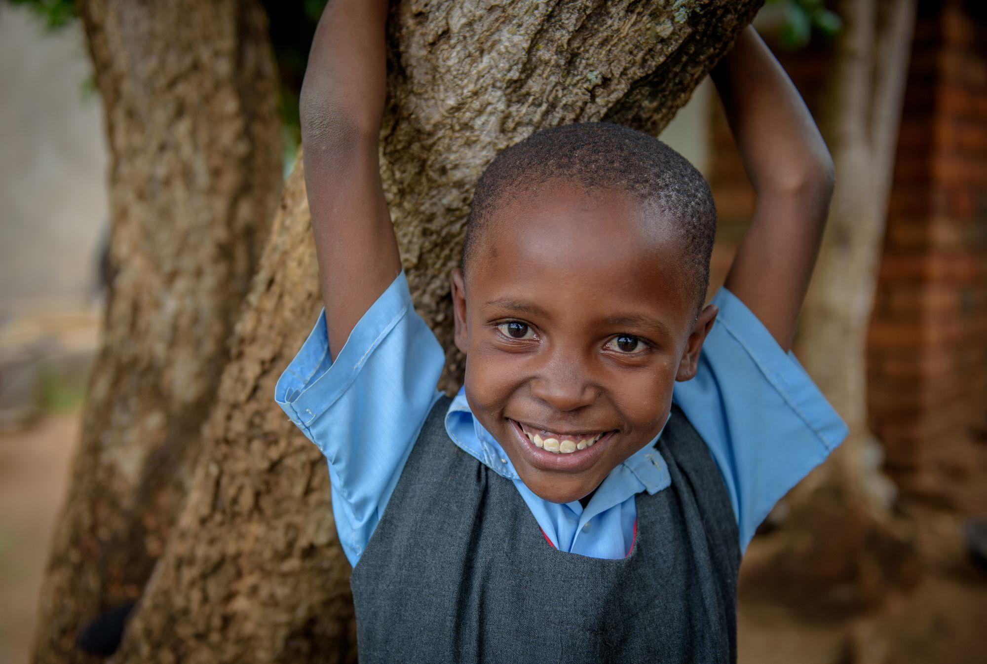 Sponsored child Mary holds on to a tree near her home.