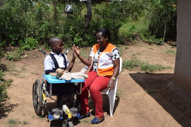 Caroline Awuor, Child Protection Facilitator at World Vision Kenya (Katito Area Programme) plays with Mercy,9, whose school performance has improved due to the wheelchair she received from the organisation. She is also able to perform chores independently