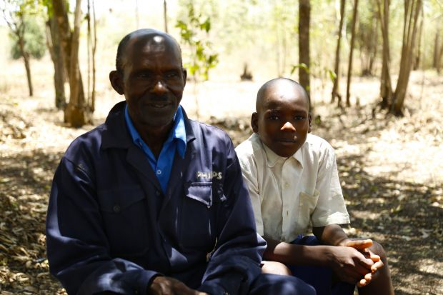 Charles with his son Biron resting in the shade of trees in the farm on a hot day.