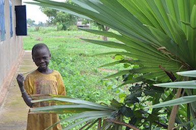 A young boy stands next to a World Vision Chad supported school for the girl-child, within Moundou region