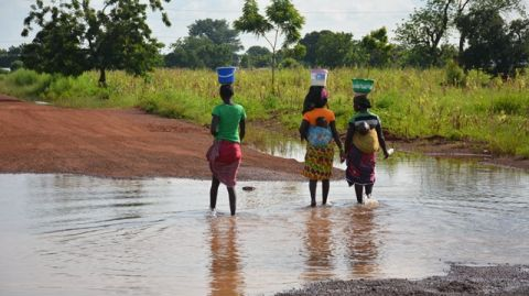 Women crossing flood waters with their babies as water is yet to recede completely