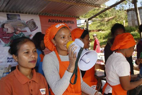 Terezinha uses a megaphone to sell her products at the market.