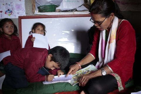Reading camp facilitator reads to child