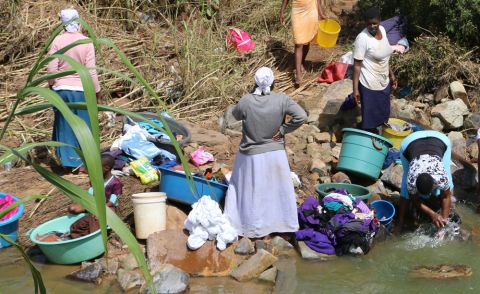 Women are resorting to a local stream which is flowing with sewer water to wash clothes.