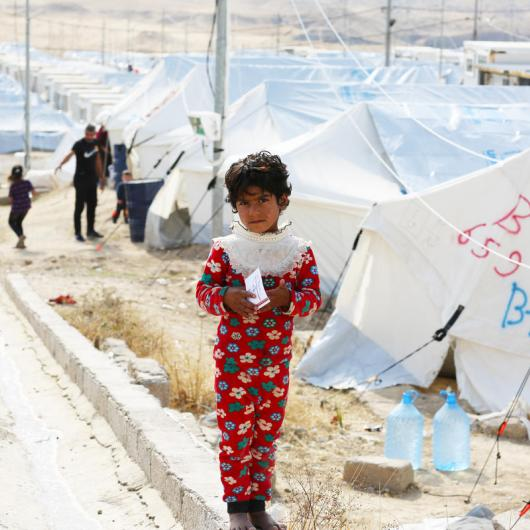 A Syrian refugee stands in front of tents