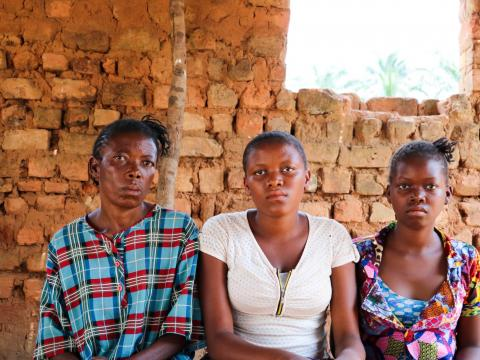 Maria sits with her daughters Joelle and Jeanette in a village in Dibaya territory. The girls walked for three months to get to Kasai Central from Tshikapa, where they grew up.