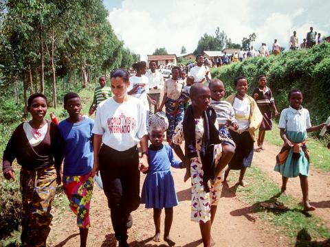 WVI Employee walking with children during Rwandan Genocide