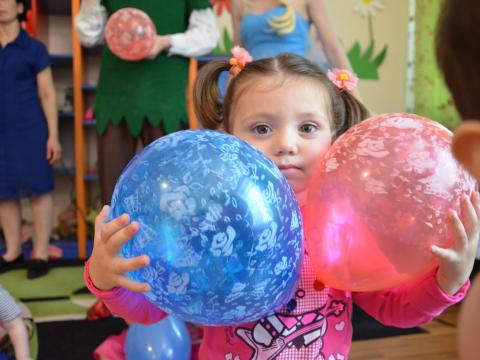 A young Georgian girl holds balloons in her classroom