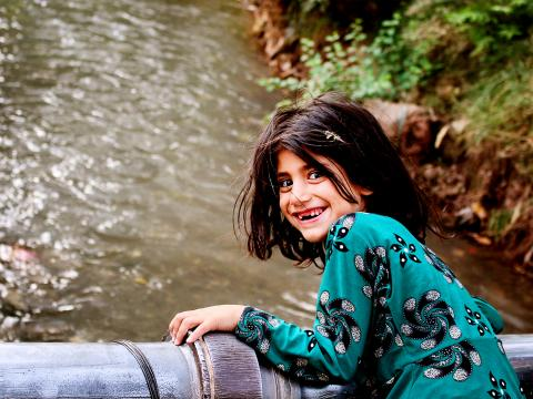 An Afghan girl stands above a river smiling