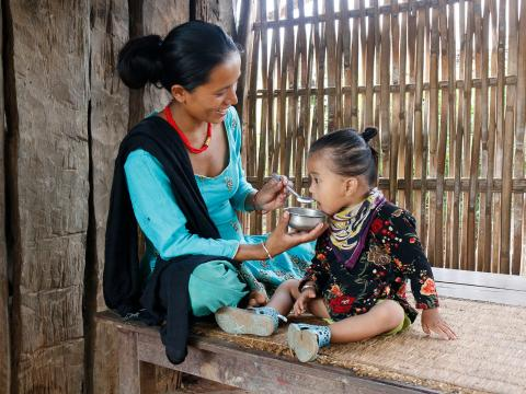 Mana feeds her child nutritious food in Nepal
