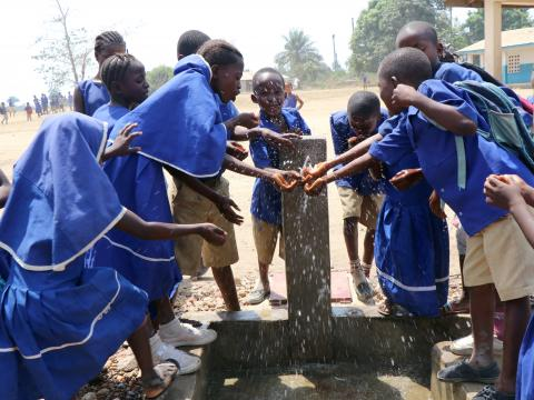 Children at Kokofele Primary Shcool enjoying safer drinking water provided by WV WASH.JPG