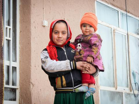 An Afghan girl holds her sibling in her arms