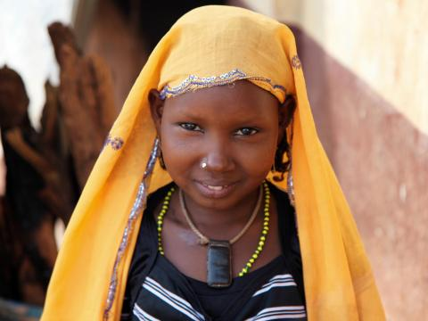 A girl in the Central African Republic stands with a yellow scarf on her head