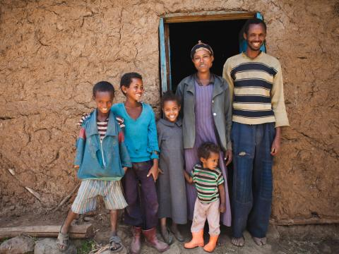 A family in Ethiopia stand outside their home