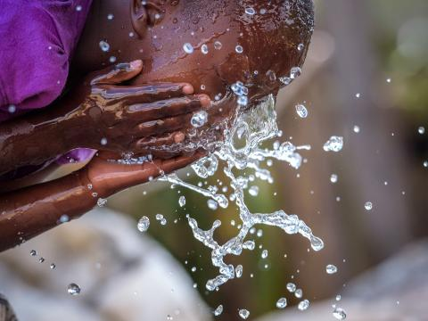 A young girl washes her face with clean water