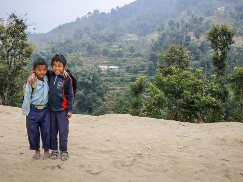 Two Nepal boys stand outside their school