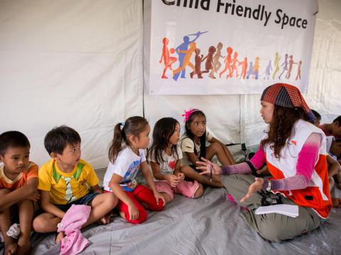 A World Vision worker speaks with children during an emergency