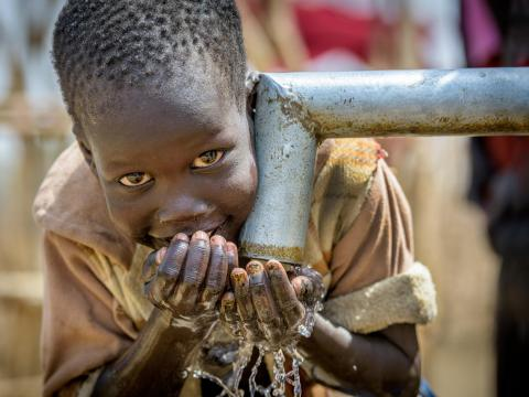 A boy in South Sudan drinks clean water