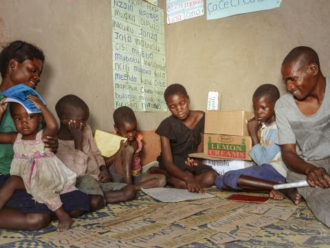 Mukonda with his family- he has four children whom he encourages to read through the reading corner and his has also taken up reading through this iniatitive.jpg