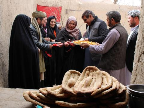 A group of Afghanistans stand around freshly made bread