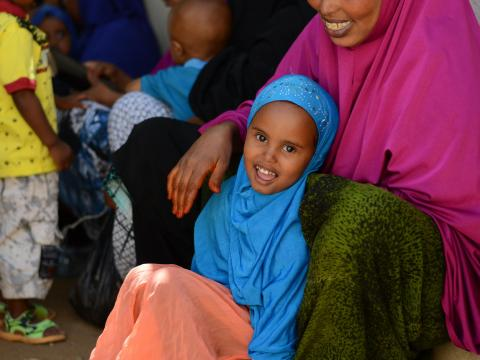 A Somali girl sits with her month