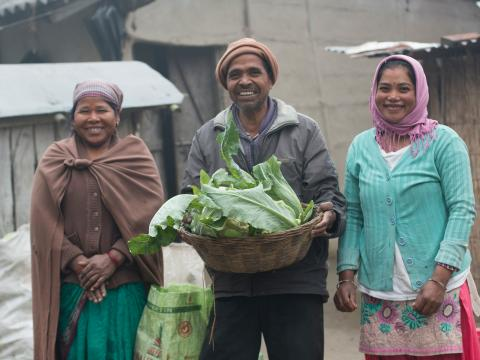 A family holds produce outside of the farm in Nepal