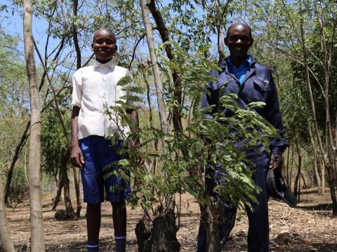 Charles Abongo (right) with his son Biron at their farm in Homabay County which has over 900 trees.