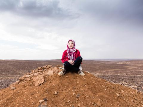 Shaima sits outside the refugee camp that she now lives