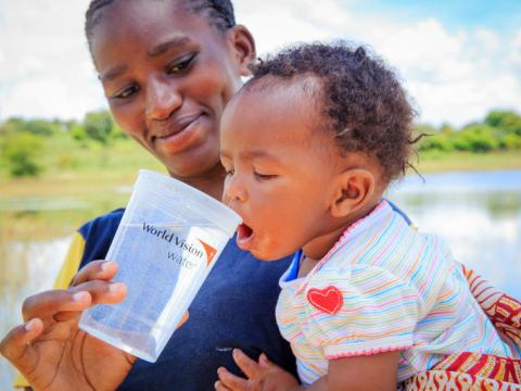 Baby Damian from Mwala, ADP Kenya, is given water from a water project WV implemented in the area.