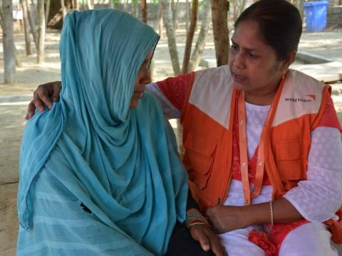 World Vision staffer sits with a Rohingya refugee