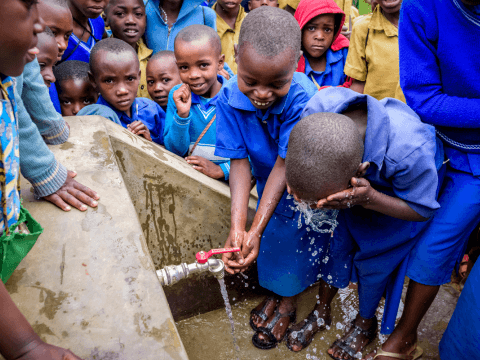 Children using clean water to wash hands and face