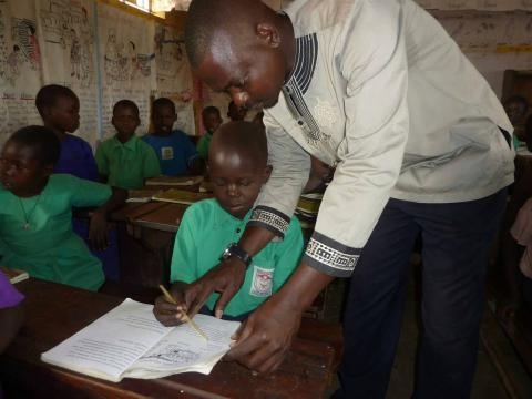 John Omara, teaching one of his students how to pronounce a word.