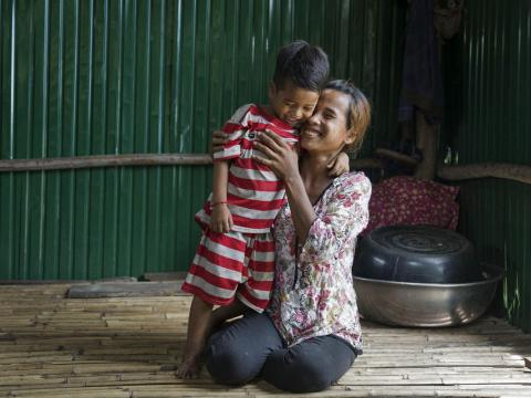 Khmer mother smiles and hugs her son