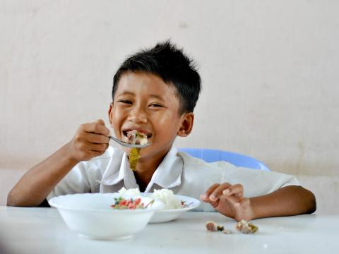 Young Khmer boy eating meal at the table