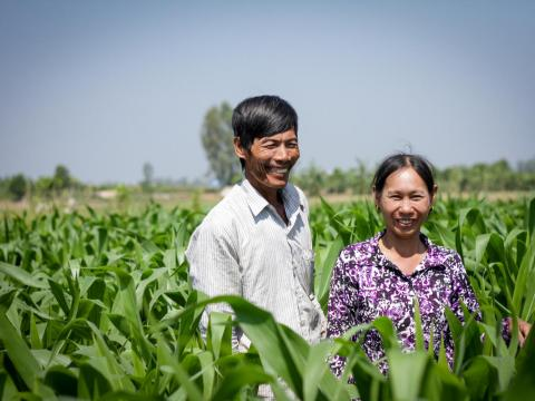 Khmer husband and wife stand in the tall grasses of their corn field