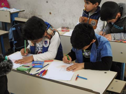 Children of grade one drawing their negative emotions during the Mandala psychosocial support session in Iraq